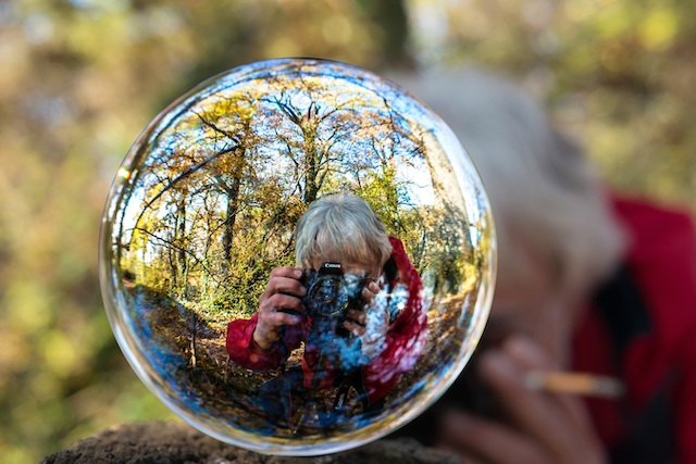 man taking photo in glass sphere